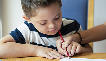 Child using red color pencil on paper